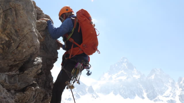 male mountaineer ascends vertical rock wall above mtns, valley - sports helmet stock videos & royalty-free footage