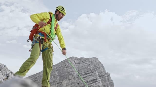 vídeos y material grabado en eventos de stock de hombre alpinista subiendo la ladera rocosa de la cima de la montaña - reloj de pulsera