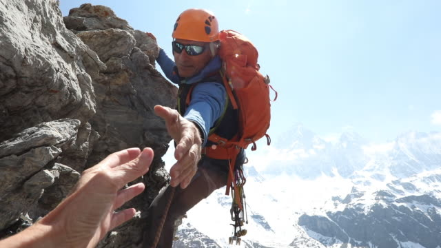 Male mountaineer climbs rock, extends helping hand to teammate