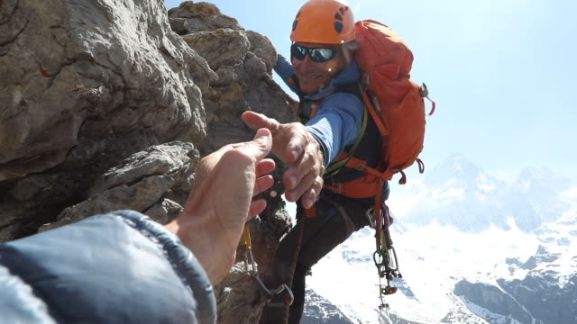 male mountaineer climbs rock, extends helping hand to teammate - safety stock-videos und b-roll-filmmaterial