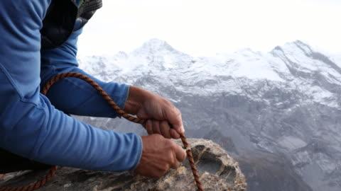 vídeos y material grabado en eventos de stock de male mountaineer cuts rope on edge of cliff, mountains - cuerda
