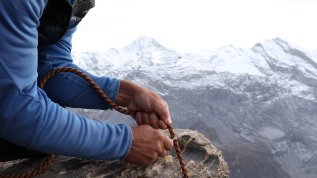 Male mountaineer cuts rope on edge of cliff, mountains