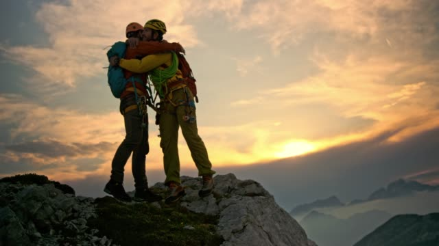 Male mountaineer extending his hand and helping friend get to the mountain top at sunset
