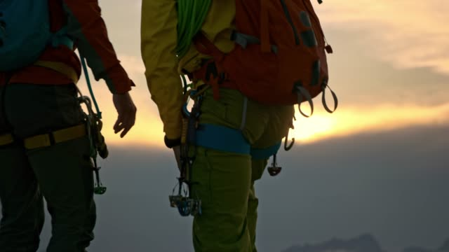 male mountaineer helping friend get to the mountain top and they watch the sunset - climbing rope stock videos & royalty-free footage