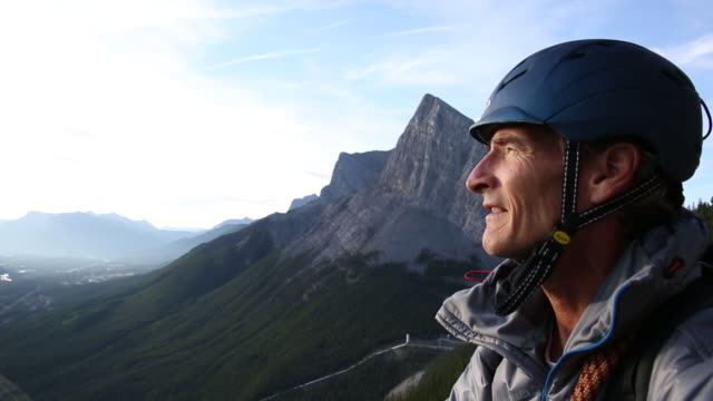 Male mountaineer looks off to mountains and valley