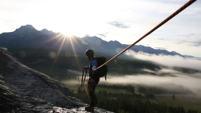 Male mountaineer prepares to rappel (abseil) into valley