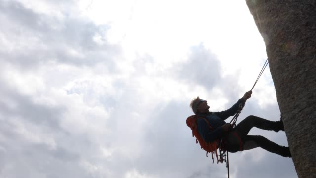 male mountaineer rappels (abseils) from rock summit - abseiling stock videos & royalty-free footage