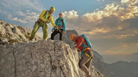 vídeos y material grabado en eventos de stock de hombre alpinista llegar a la cima de la montaña y celebrando con sus dos colegas - casco herramientas profesionales
