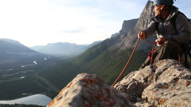 male mountaineer takes in rope before belaying teammate - belaying stock videos & royalty-free footage