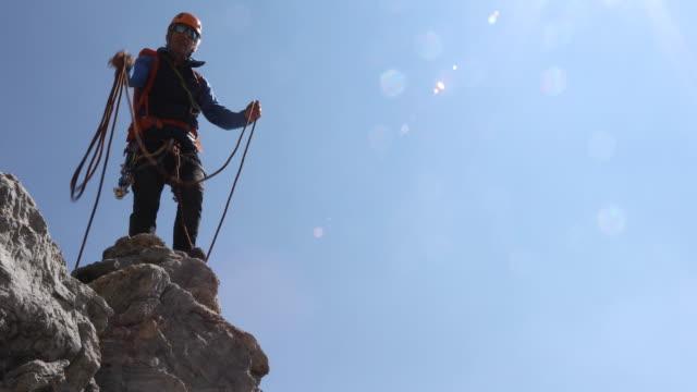vídeos y material grabado en eventos de stock de male mountaineer tosses rope to teammate, mountains - one mature man only