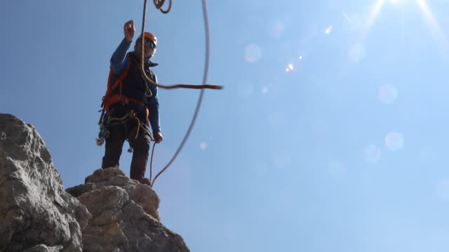 Male mountaineer tosses rope to teammate, mountains