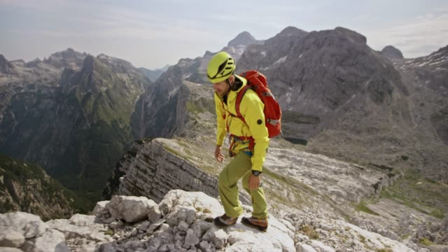 male mountaineer walking on a rocky mountain ridge in sunshine - wrist watch stock videos & royalty-free footage