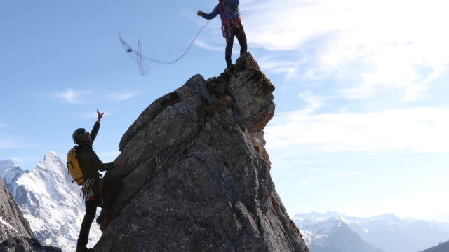 male mountaineers climb rock pinnacle, leader tosses rope - rope stock videos & royalty-free footage