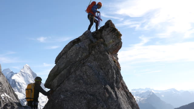 male mountaineers climb rock pinnacle, mountains below - rope stock videos & royalty-free footage