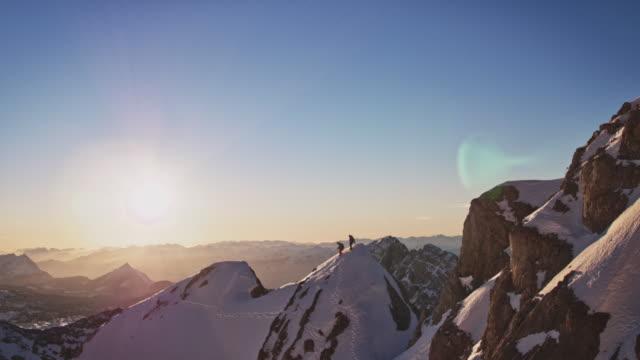 männliche bergsteiger auf schneebedecktem grat - schöne natur stock-videos und b-roll-filmmaterial