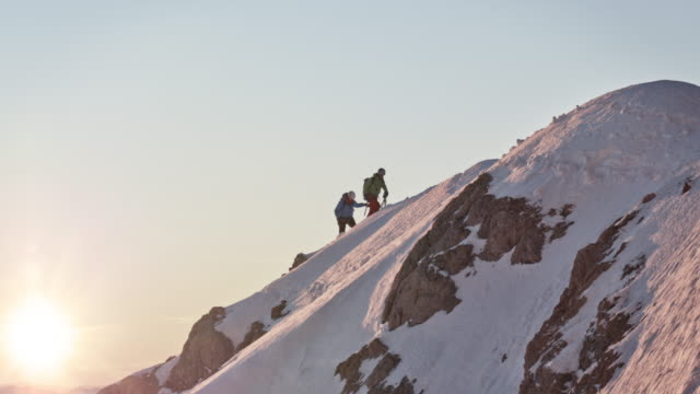 male mountaineers walking on snow covered ridge - exploration stock videos & royalty-free footage