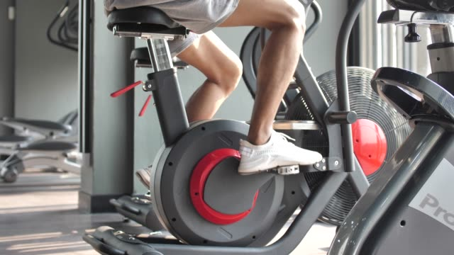 male muscular exercising on a exercise bike in gym - exercise bike stock videos & royalty-free footage