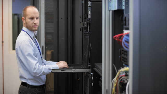 DS Male network engineer working on a computer in the server room