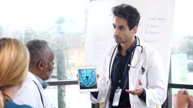 vídeos de stock e filmes b-roll de male neurologist confidently discusses a patient's brain mri - neurologista