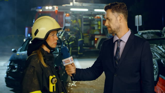 male news reporter interviewing a female firefighter at the scene of a car accident at night - heroes stock videos & royalty-free footage