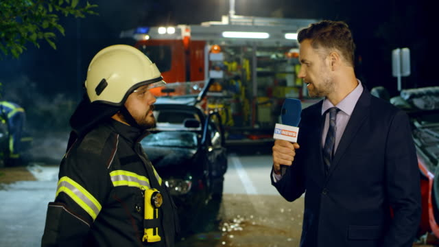 Male news reporter interviewing a male firefighter at the scene of a car accident at night