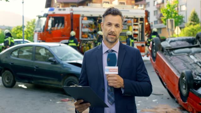 vídeos de stock, filmes e b-roll de masculino repórter relatórios da cena de um acidente de carro - jornalista