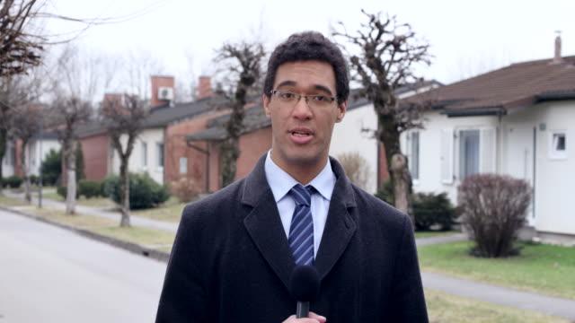 vidéos et rushes de journaliste de nouvelles mâle reporting direct du champ - chemise et cravate