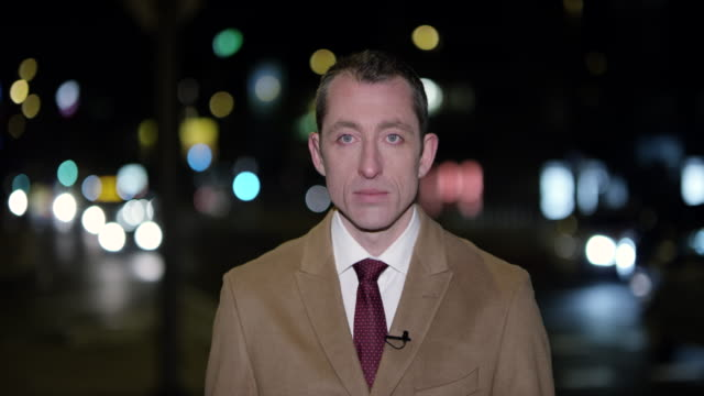 male news reporter reporting live to the studio from the city at night - tv reporter stock videos & royalty-free footage