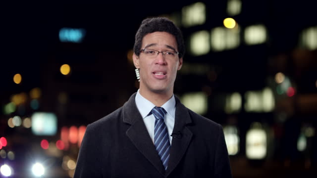 male news reporter reporting live to the studio from the city center at night - tv reporter stock videos & royalty-free footage