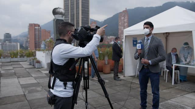vídeos y material grabado en eventos de stock de locutor masculino frente a la cámara reportando desde un soporte de vacunación covid-19 durante la pandemia mientras los pacientes hacen fila para su vacuna - journalist