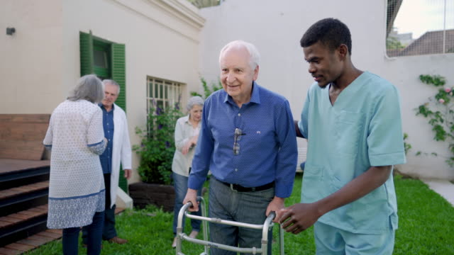 male nurse assisting senior man with mobility walker in nursing home - orthopedic equipment stock videos & royalty-free footage