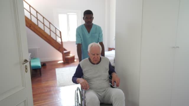 vidéos et rushes de infirmière mâle aidant un vieil homme dans la maison de pépinière dans le fauteuil roulant - infirmier