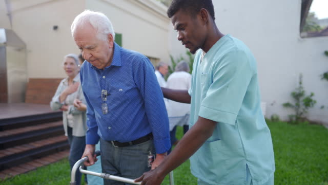 male nurse helping senior man with mobility walker outdoor - orthopedic equipment stock videos & royalty-free footage