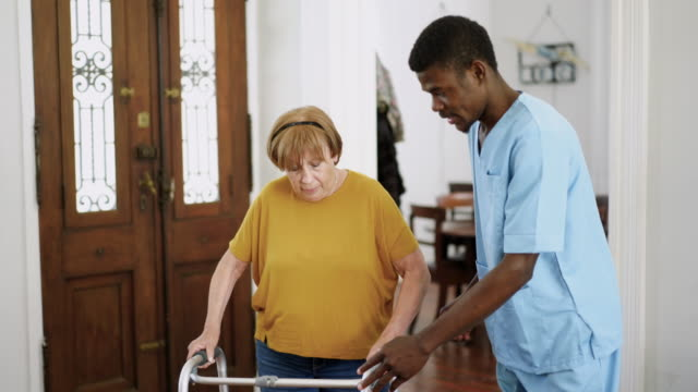 vídeos de stock e filmes b-roll de male nurse helping senior woman with mobility walker in the nursing home - chamada a casa