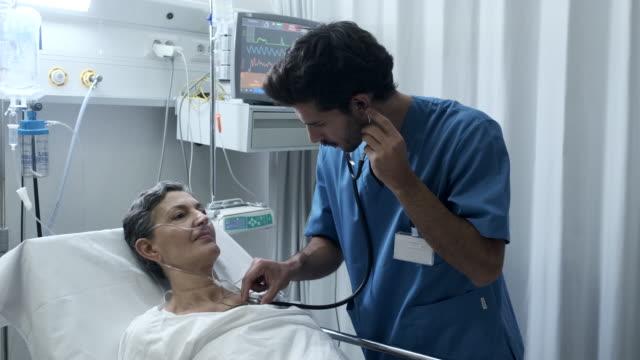 un'infermiera maschio sta ascoltando con uno stetoscopio il petto di un paziente - apparato respiratorio video stock e b–roll