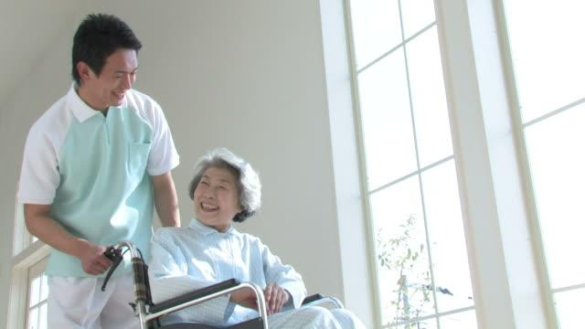 LA Male nurse pushing patient in wheelchair