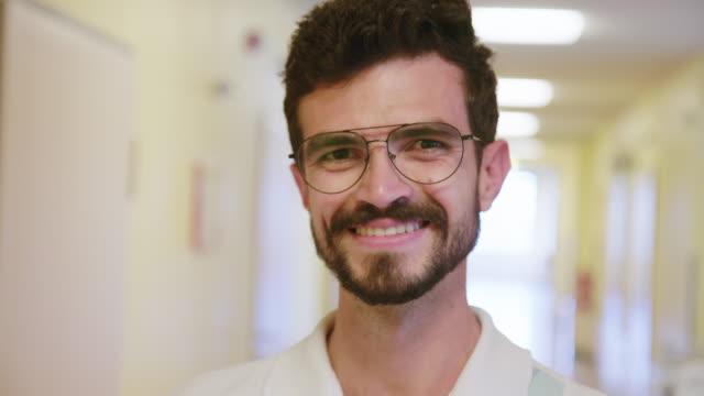 vídeos de stock, filmes e b-roll de enfermeira masculina que sorri no corredor do hospital - barba
