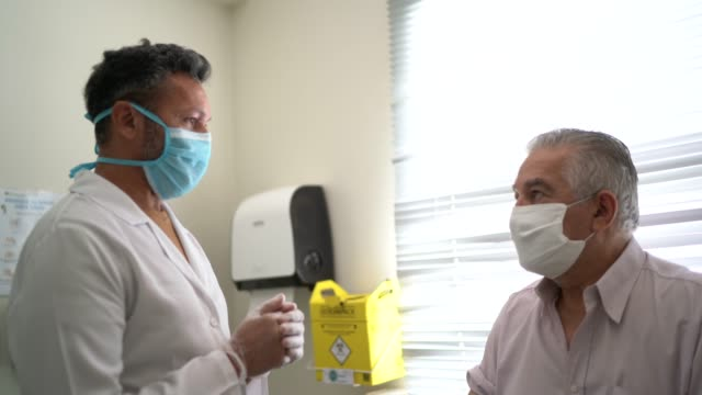 male nurse talking to a patient, preparing for vaccination - flu vaccine stock videos & royalty-free footage