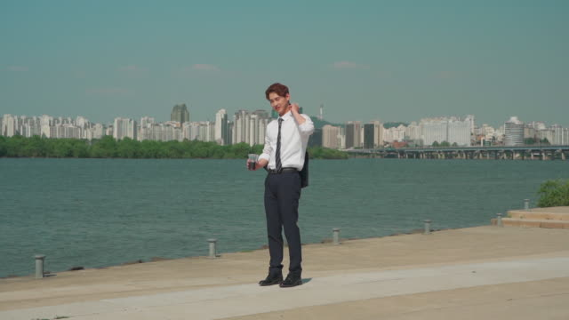 a male office worker carrying the jacket on his shoulder in the han river park - oberhemd stock-videos und b-roll-filmmaterial