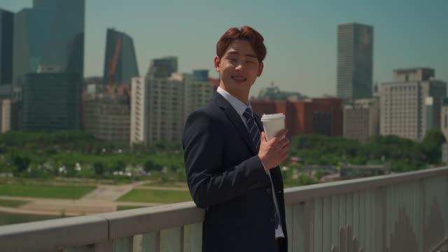 stockvideo's en b-roll-footage met a male office worker drinking a cup of coffee on the bridge - overhemd en stropdas