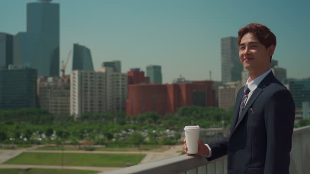 a male office worker holding a cup of coffee on the bridge - 背広点の映像素材/bロール
