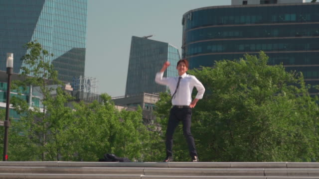 vídeos de stock e filmes b-roll de a male office worker jumping and shaking his fist in the park - membro humano