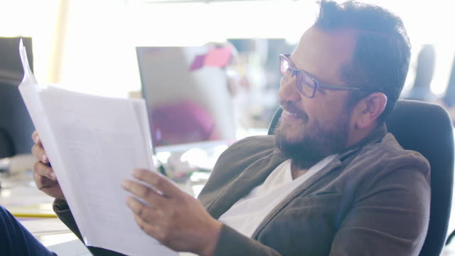 Male office worker reading document turning to camera and smiling