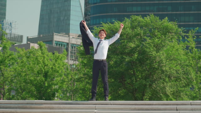 a male office worker spreading out his arms in the han river park - hemd und krawatte stock-videos und b-roll-filmmaterial