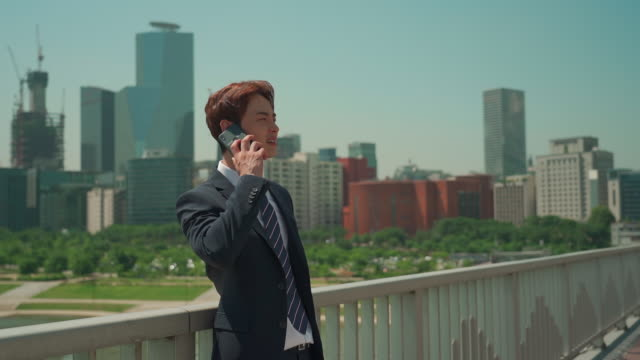 stockvideo's en b-roll-footage met a male office worker talking over the phone on the bridge - overhemd en stropdas