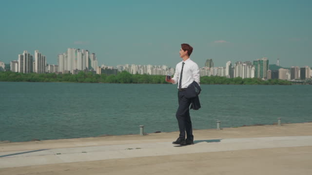 a male office worker walking in the han river park - hemd und krawatte stock-videos und b-roll-filmmaterial