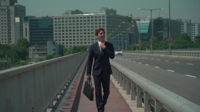 A male office worker walking on the bridge