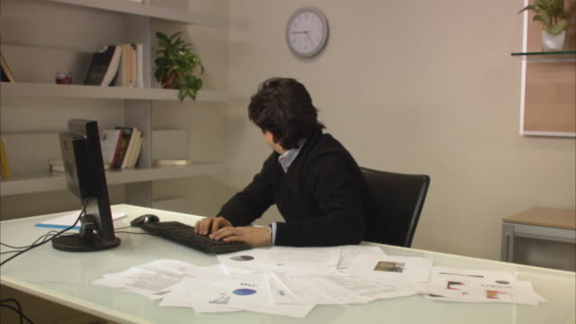 ms male office worker working in office, looking at clock and scattering papers on table with head in hands / new york city, new york, usa - checking the time stock videos & royalty-free footage