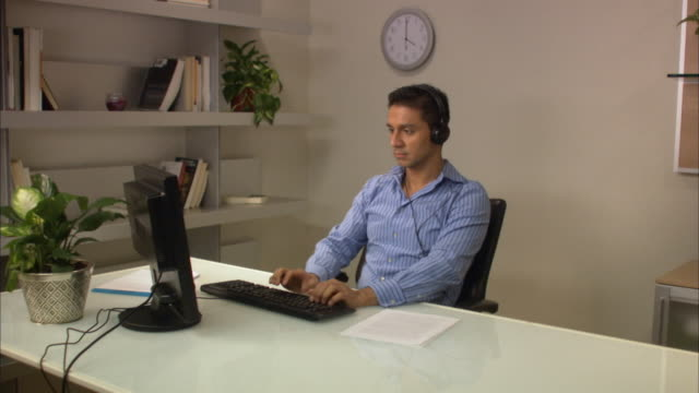 ms male office worker working on computer at desk in office listening to headphones / new york city, new york, usa - dedizione video stock e b–roll