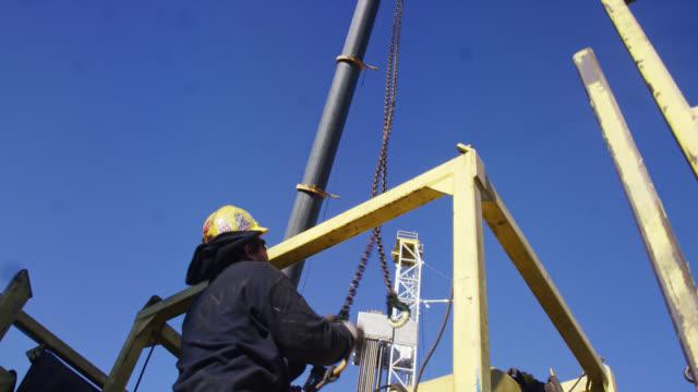 vídeos de stock, filmes e b-roll de um trabalhador do campo de petróleo masculino quebra uma plataforma e carrega-o em um trailer em um local de perfuração de óleo e gás em um dia ensolarado - boca de poço